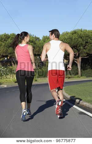 Back View Of Young Couple Running On Road