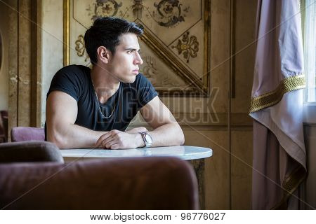 Relaxed Young Man Sitting Comfortably at Table