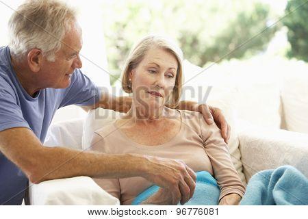 Husband Comforting Senior Woman Feeling Unwell Resting Under Blanket