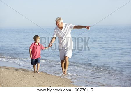 Grandfather And Grandson Enjoying Walk Along Beach