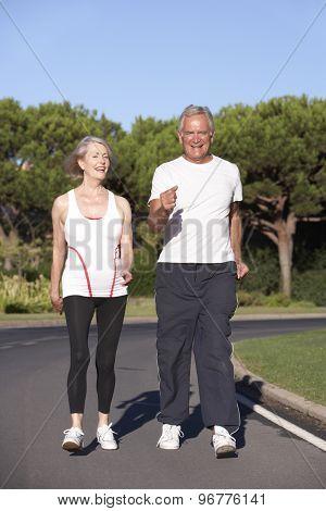 Senior Couple Running On Road