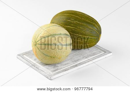 fresh melons on wooden cutting board