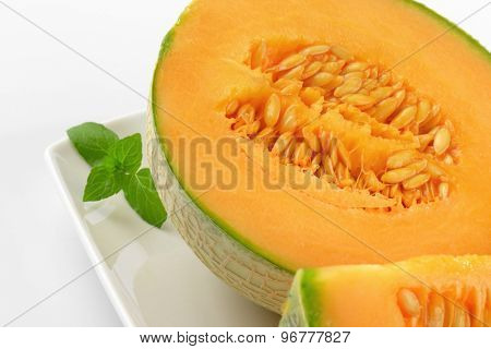 detail of halved cantaloupe melon on white plate