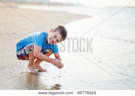 Little Boy Playing With Sand On Coast