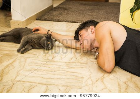 Young Man Lying on Floor Petting Pet Cat