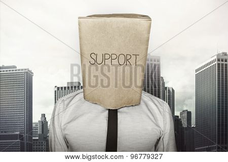 Support text on brown paper bag which businessman has on head