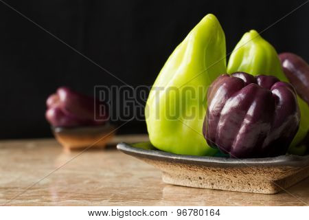 Purple And Green Peppers On A Marble Background