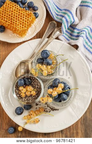 Milk Pudding With Chia Seeds, Blueberries And Currants In A Batch Jars On Wooden Background