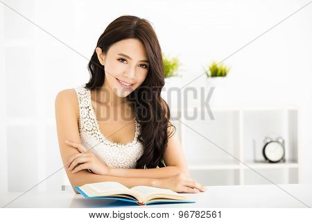 Happy young woman reading book in living room