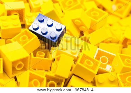 Pile of yellow color building blocks with selective focus and highlight on one particular blue block