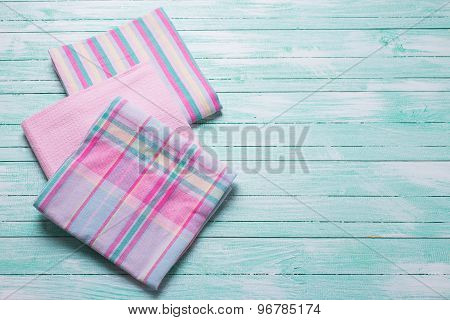 Pink  Kitchen Towels  On Turquoise  Wooden Background.
