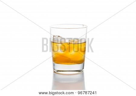 Glass of cold whiskey on the rocks, isolated in white