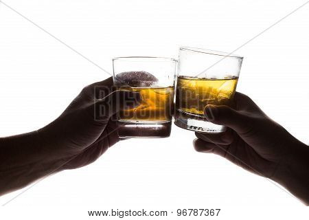 Silhouette of two hands toasting whiskey on the rock, with isolated background