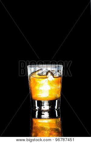 Ice cold whiskey on the rock on a dark background in portrait orientation