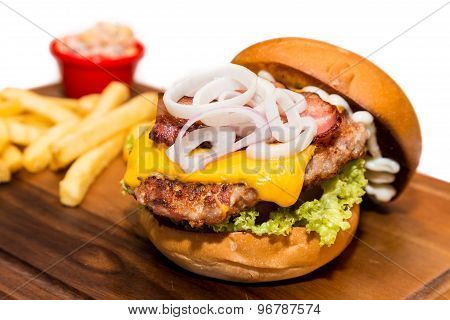 Delicious pork burger with cheese, vegetable and served with fries