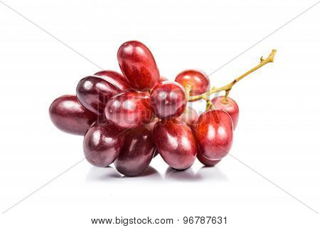 A bunch of juicy, sweet and seedless red crimson grape isolated in white