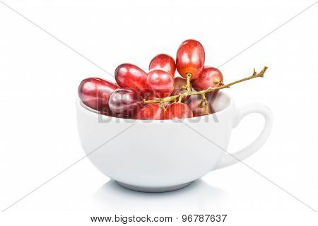 A cup of sweet, juicy and seedless red crimson grape isolated in white