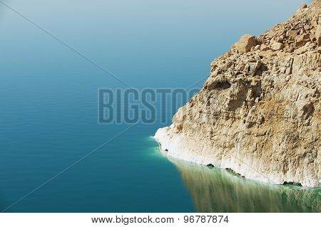 View to the cliff at the Dead sea shore with reflection in the water in Jordan.