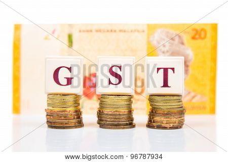 GST or Goods and Services Tax concept with stack of coins and Malaysia Ringgit currency as backdrop
