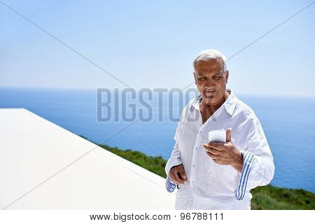 senior man using smart phone outdoor with ocean view background