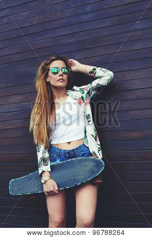 Young trendy woman in sunglases posing with her longboard enjoying good day in summer