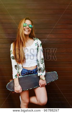 Smiling teenage girl in sunglases holding her skateboard while standing against wooden wall