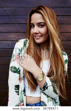 Portrait of a beautiful fashionable young woman with long hair posing outdoors in summer