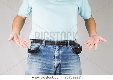 Man in jeans with empty pockets with discouraging gesture