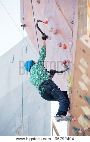 Man climbs upward on ice climbing competition