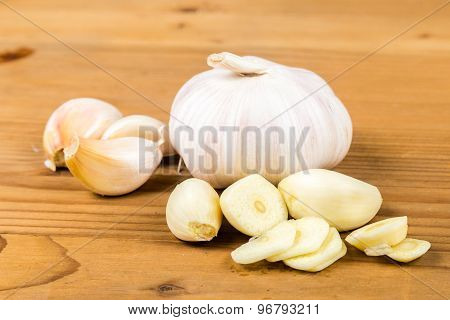 Peeled and sliced garlic cloves with whole garlic bulb and cloves as background