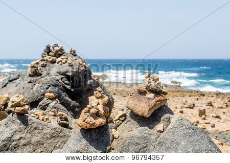 Stones Stacked On Black Volcanic Rock
