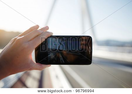 Person taking a photo of beautiful sunset using smart phone camera of outdoors