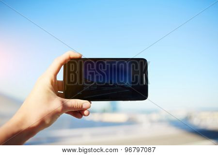 Tourist hand holding cell phone while taking a photograph of landscape in travel