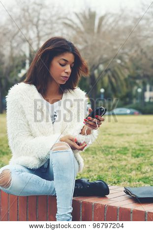 Stylish attractive afro american woman holding smart phone while sitting in the park outdoors