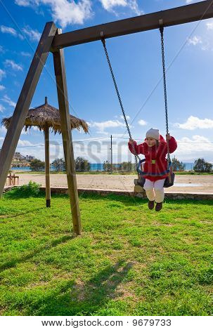 The Little Girl On A Swing Against The Backdrop Of Sea And Sky With Clouds In The Winter.