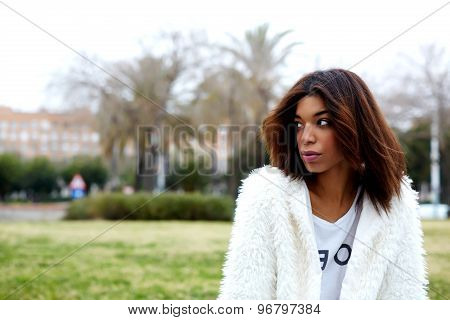 Young trendy female hipster in stylish clothing pensive looking away while sitting in the park