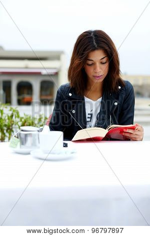 Portrait of charming afro american woman reading novel or book during her recreation time at weekend