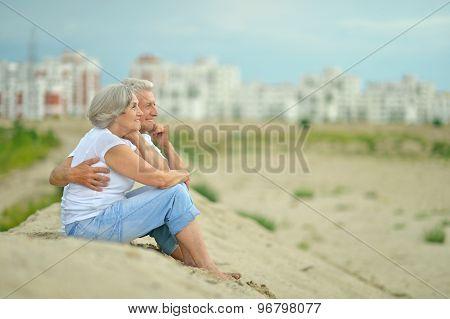 Elderly couple sitting on sand
