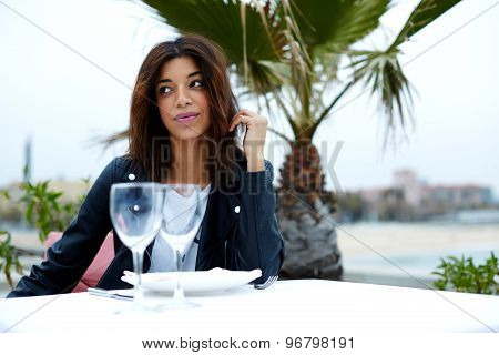 Female tourist smoking cigarette while enjoying her recreation time in restaurant on seashore