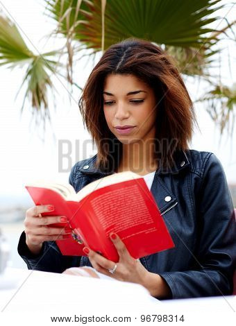 Young lovely woman sitting at coffee shop terrace pensive reading interesting book outdoors