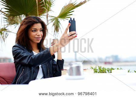 Stylish afro american woman taking self portrait with smartphone feeling good and happy