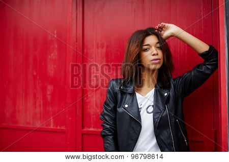 Portrait of attractive black female posing on red wall background in the city
