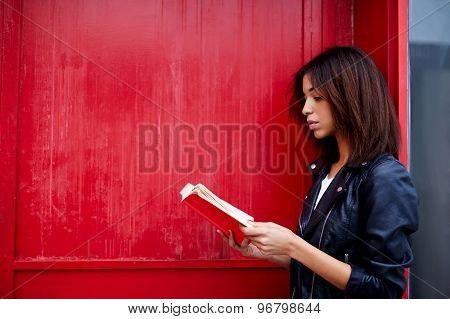 Pretty afro american woman read literature while standing in the city on red wall background