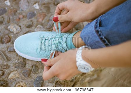 Women's Hands With A Red Manicure Knotted Laces On Athletic Shoes