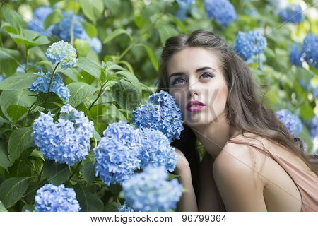 Portrait Of Beautiful Woman And Blue Flowers