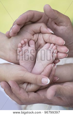 Happy young family of mother and father holding bare feet