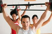 image of gym workout  - Group of three people exercising using barbells in the gym to gain strength and fitness - JPG