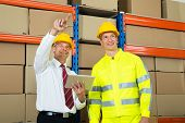 stock photo of warehouse  - Warehouse Worker And Manager Checking The Inventory In A Large Warehouse - JPG