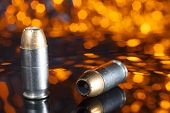 picture of hollow  - Cartridges for a handgun with hollow point bullets and an orange background - JPG