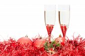 pic of sparkling wine  - two glasses of sparkling wine and angel figure at red Christmas balls and tinsel isolated on white background - JPG
